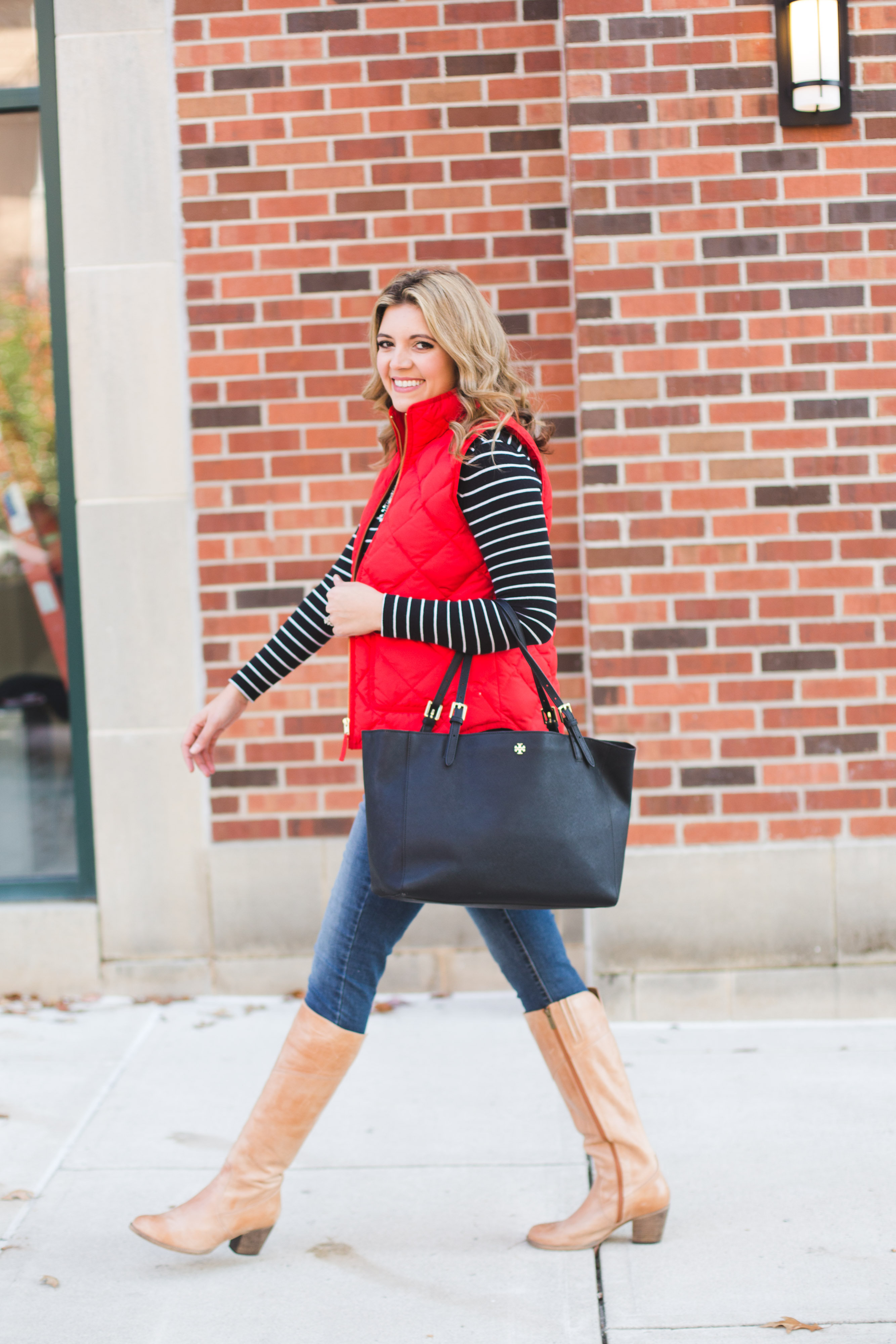 holiday shopping style - red puffer vest, stripe tee, skinny jeans and tan heeled boots | www.bylaurenm.com