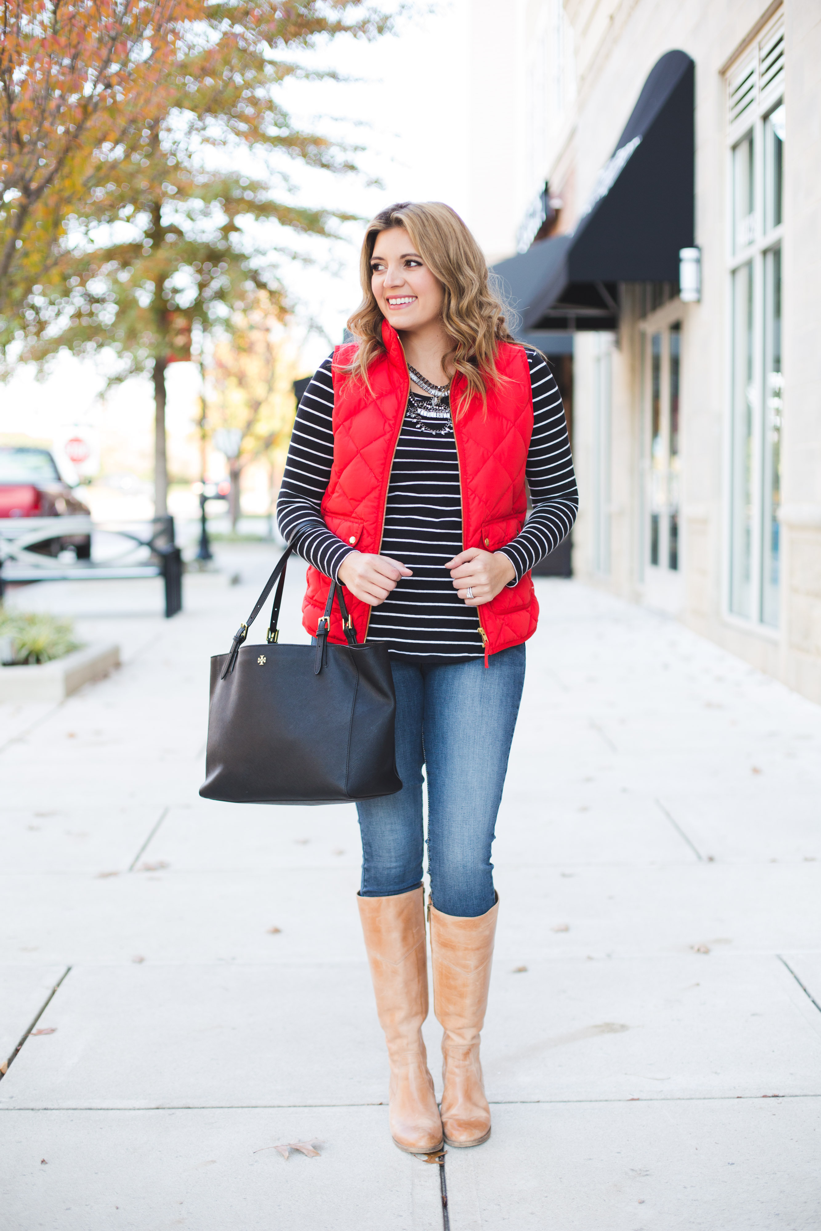 red puffer vest outfit - red excursion vest, striped tee, skinny jeans, tan boots | www.bylaurenm.com
