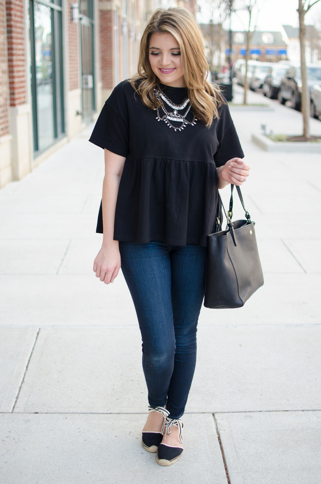 ruffle hem tee outfit - black oversized peplum top with skinny jeans and lace up espadrilles | Click through for more cute weekend outfit ideas or to shop this look! www.bylaurenm.com