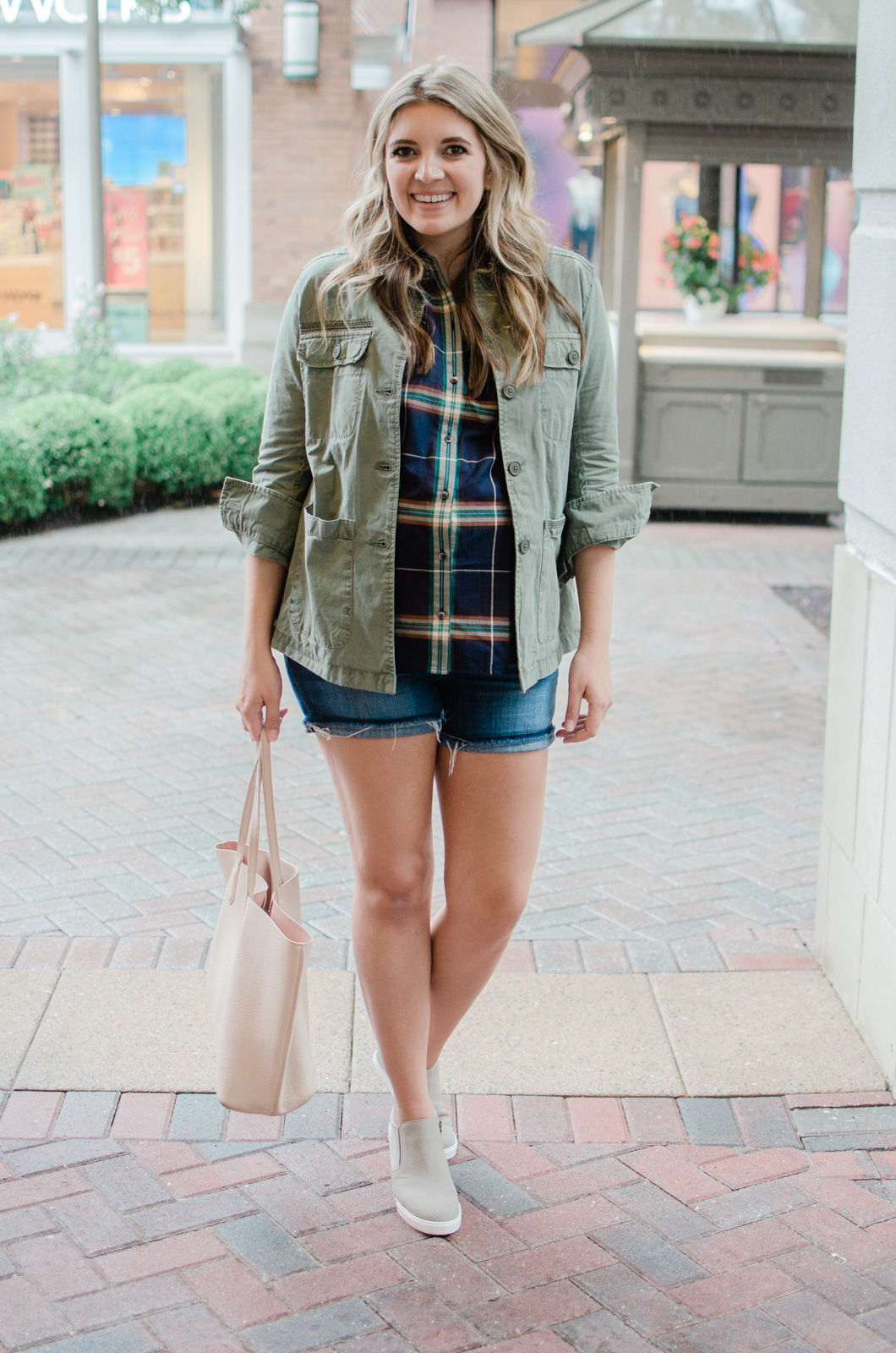 early fall maternity style - the perfect fall transition bump outfit: green utility vest, plaid top, denim shorts, and wedge sneakers | bylaurenm.com