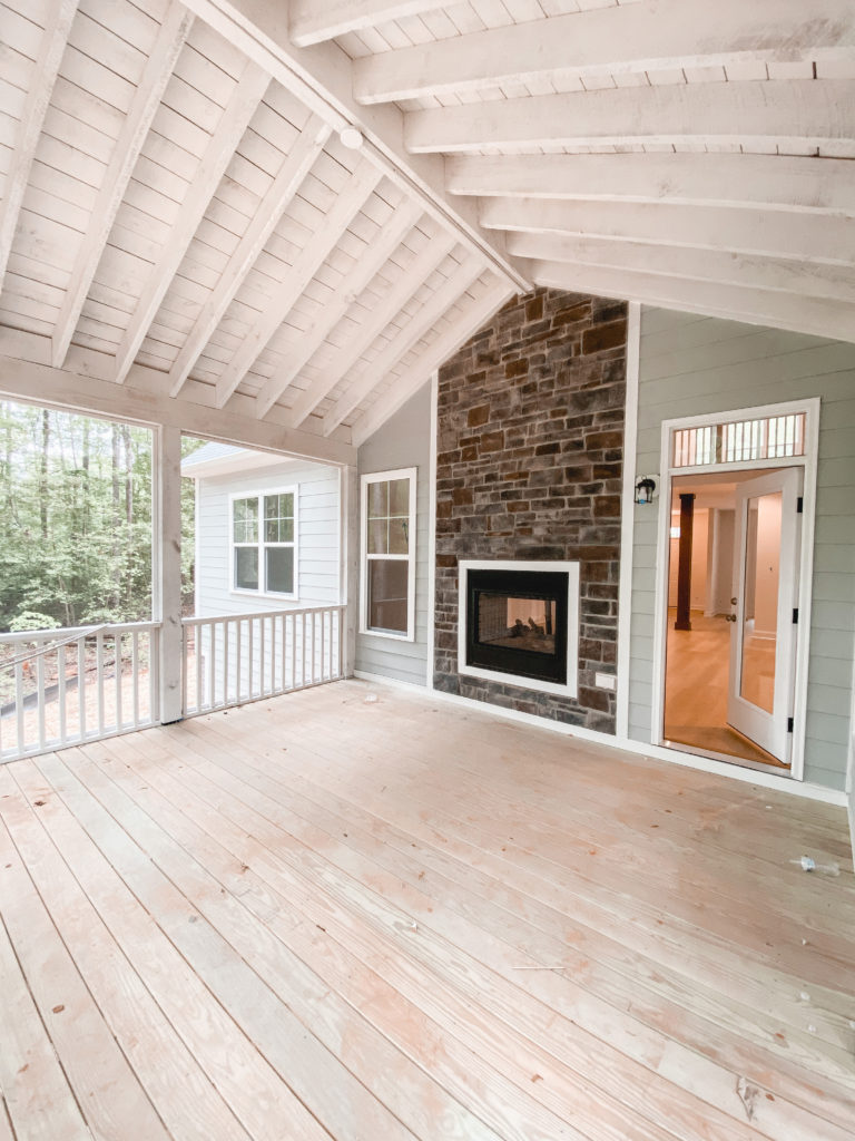 Virginia blogger, Lauren Dix, shares her screened in porch with stone fireplace in her outdoor furniture inspiration post.